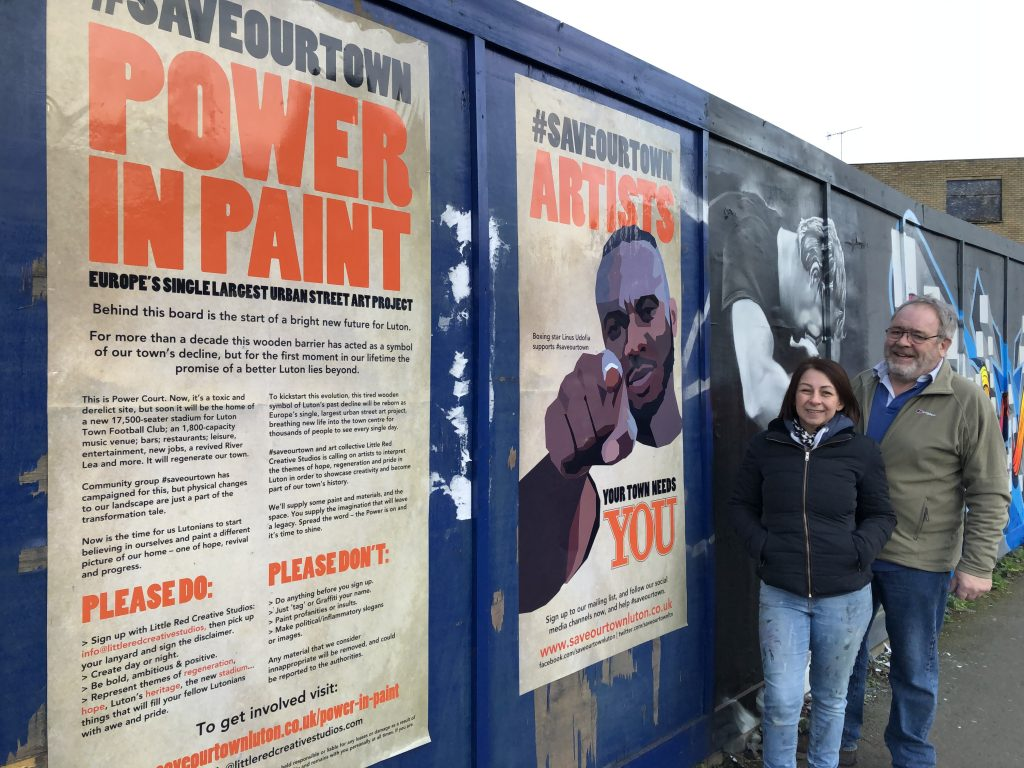 Andy King, vice chairman of #saveourtown and Aimi Rix, Director of Little Red Creative Studios, next to the Linus Udofia Power in Paint signs, which have been posted on the Power Court hoarding boards