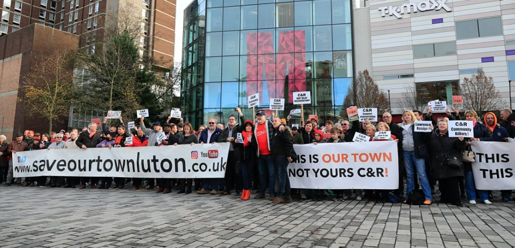 Lutonians hold a #saveourtown banner during the protest against Capital & Regional outside The Mall